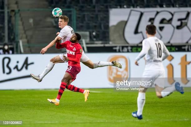 Matthias Ginter of Borussia Moenchengladbach and Emmanuel Dennis of 1. FC Koeln battle for the ball during the Bundesliga match between Borussia...