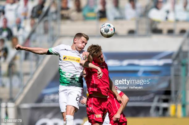 Matthias Ginter of Borussia Moenchengladbach and Marius Bülter of Union Berlin battle for the ball during the Bundesliga match between Borussia...