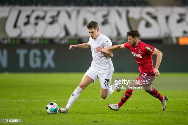 Matthias Ginter of Borussia Moenchengladbach and Salih Özcan of 1. FC Koeln battle for the ball during the Bundesliga match between Borussia...