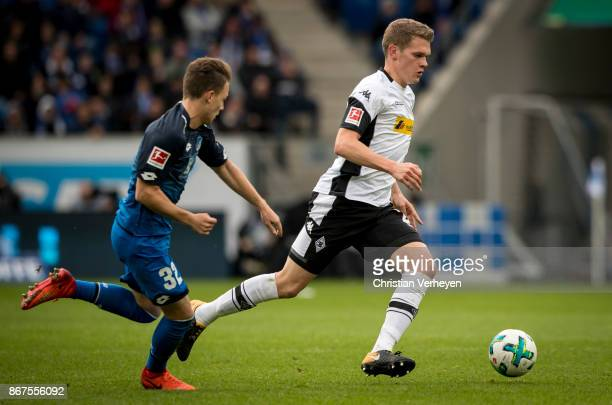 Matthias Ginter of Borussia Moenchengladbach is chased by Dennis Geiger of 1899 Hoffenheim during the Bundesliga match between TSG1899 Hoffenheim and...