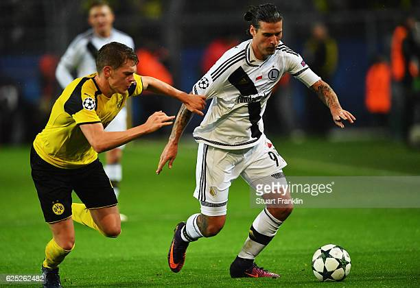Matthias Ginter of Dortmund is challenged by Aleksandar Prijovic of Warsaw during the UEFA Champions League match between Borussia Dortmund and Legia...
