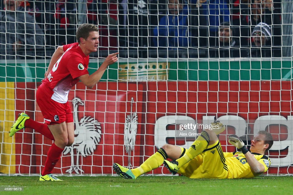 Matthias Ginter of Freiburg celebrates his team's first goal as goalkeeper Bernd Leno of Leverkusen reacts during the German Cup Round of 16 match between SC Freiburg and Bayer Leverkusen at MAGE SOLAR Stadium on December 4, 2013 in Freiburg im Breisgau, Germany.