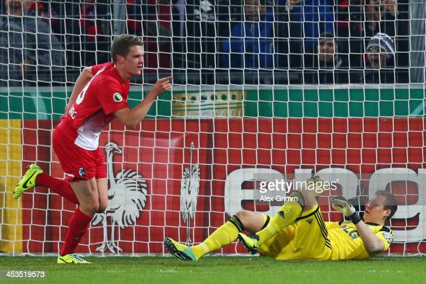 Matthias Ginter of Freiburg celebrates his team's first goal as goalkeeper Bernd Leno of Leverkusen reacts during the German Cup Round of 16 match...