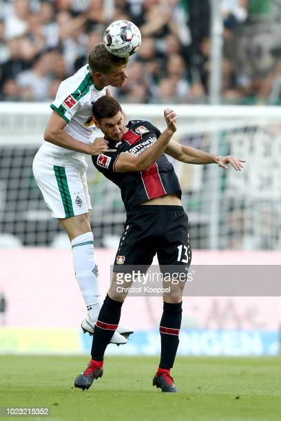 Matthias Ginter of Moenchengladbach and Lucas Alario of Leverkusen go up for a header during the Bundesliga match between Borussia Moenchengladbach...