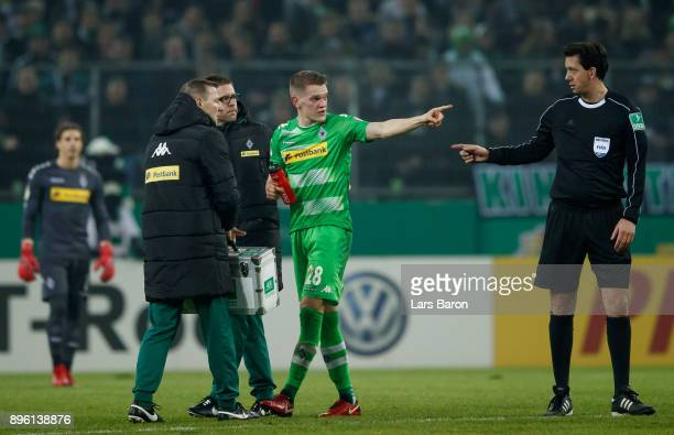 Matthias Ginter of Moenchengladbach gestures with referee Manuel Graefe during the DFB Cup match between Borussia Moenchengladbach and Bayer...