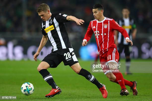 Matthias Ginter of Moenchengladbach is chased by James Rodriguez of Bayern Muenchen during the Bundesliga match between Borussia Moenchengladbach and...