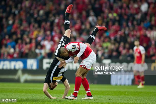 Matthias Ginter of Moenchengladbach is fouled by Robin Quaison of Mainz during the Bundesliga match between 1. FSV Mainz 05 and Borussia...