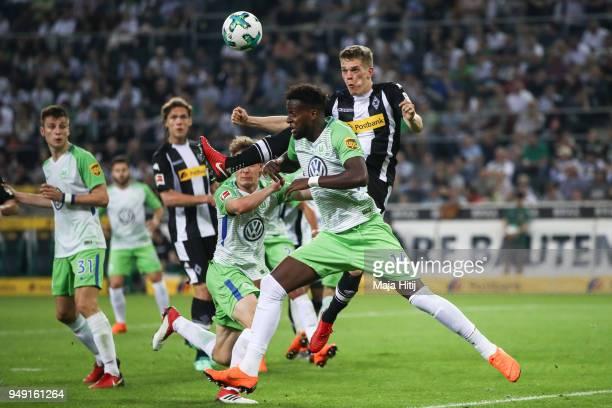 Matthias Ginter of Moenchengladbach jumps for the ball next to Divock Origi of VfL Wolfsburg during the Bundesliga match between Borussia...