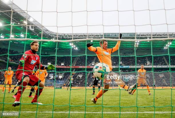 Matthias Ginter of Moenchengladbach scores his teams third goal against Oliver Baumann of Hoffenheim during the Bundesliga match between Borussia...