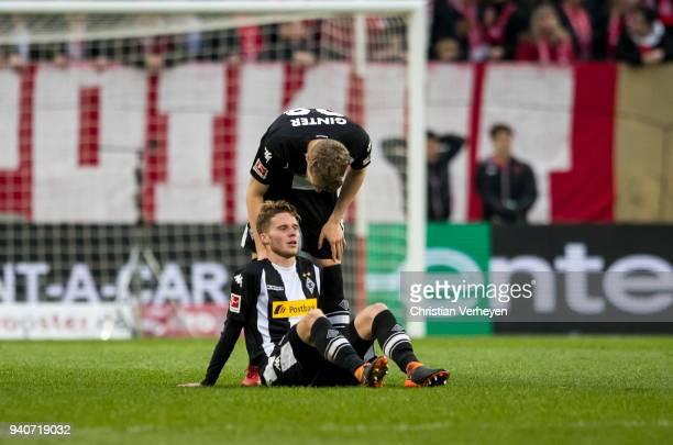 Matthias Ginter talks to injured Nico Elvedi of Borussia Moenchengladbach during the Bundesliga match between 1 FSV Mainz 05 and Borussia...