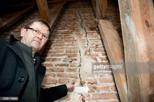 Matthias Guertler priest of the 700 year old 'Dom St Nikolai' shows a crack in the brickwork in Greifswald Germany 29 January 2013 25 years ago the...