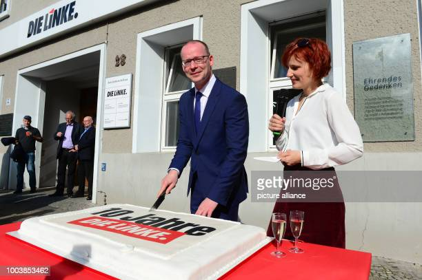 Matthias Hohn Federal Secretary General of the political party 'The Left' and Chairwoman Katja Kipping cut a birthday cake during the reception for...