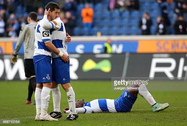 Matthias Kuehne of Duisburg hugs Branimir Bajic as Kingsley Onuegbu lies on the pitch after the Third League match between MSV Duisburg and SV Wehen...