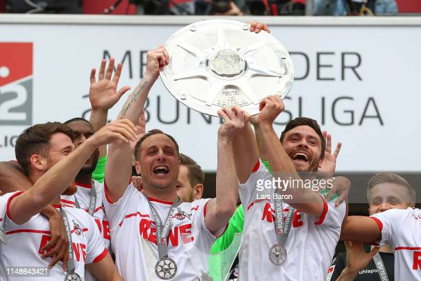 Matthias Lehmann and Jonas Hector of FC Koeln lift the Second Bundesliga trophy at the end of the Second Bundesliga match between 1. FC Koeln and SSV...