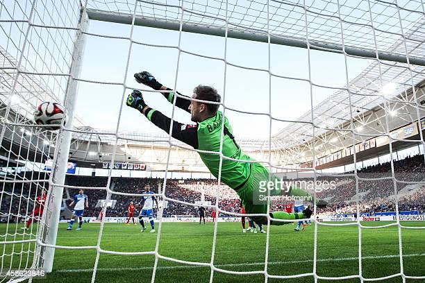 Matthias Lehmann of Koeln scores his team's second goal against goalkeeper Oliver Baumann of Hoffenheim during the Bundesliga match between 1899...