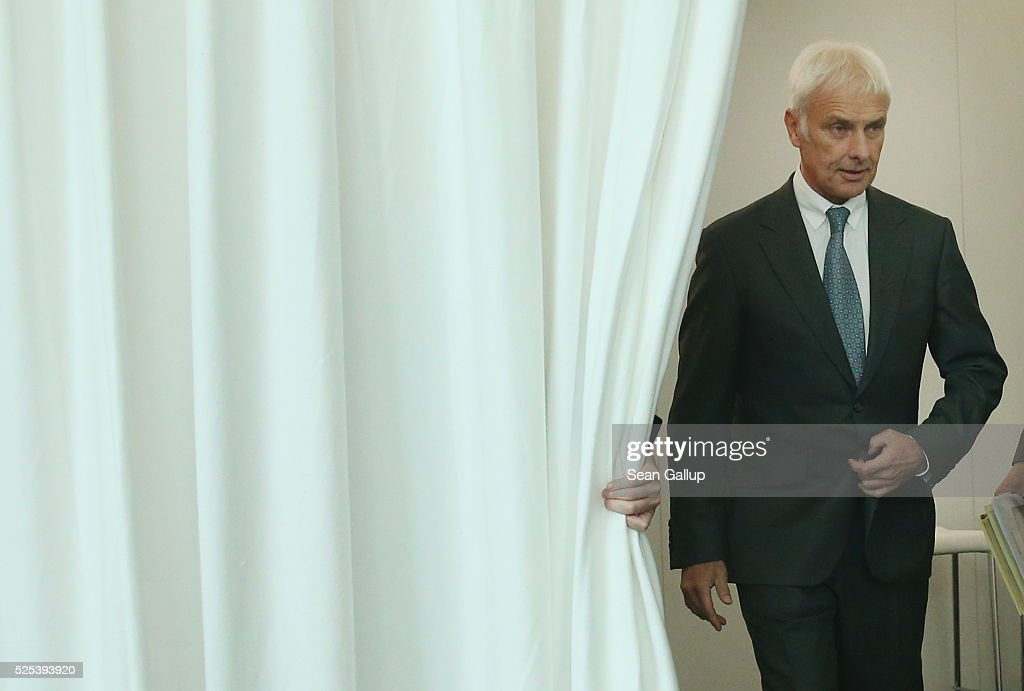 Matthias Mueller, CEO of German automaker Volkswagen AG, emerges from behind a curtain to speak to television reporters following the company's annual press conference on April 28, 2016 in Wolfsburg, Germany. Volkswagen is facing high costs and stiff penalties, including the possible buyback of up to 500,000 cars it sold in the USA, as a reult of VW's diesel emissions scandal.