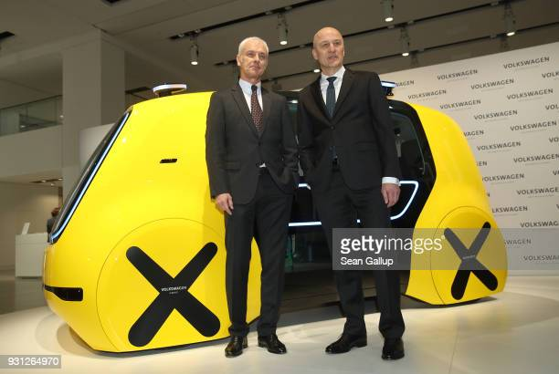 Matthias Mueller Chairman of German automaker Volkswagen AG and VW Chief Financial Officer Frank Witter pose at a Volkswagen Sedric autonomous car as...