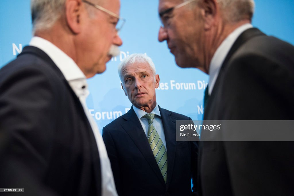 Matthias Mueller, Chairman of Volkswagen AG (C), Dieter Zetsche, chairman of German car maker Daimler AG and Governor of Baden-Wuerttemberg Winfried Kretschmann talk after a news conference after the Diesel Conference on August 2, 2017 in Berlin, Germany. Germany's car industry faces existential crisis after the emissions scandal and a cartels investigation.