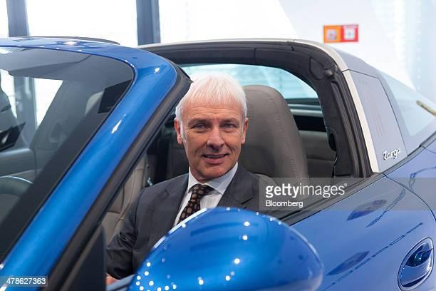 Matthias Mueller chief executive officer of Porsche AG poses for a photograph in a Porsche 911 Targa 4S automobile during a news conference to...