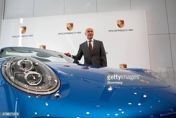 Matthias Mueller chief executive officer of Porsche AG poses for a photograph beside a Porsche 911 Targa 4S automobile during a news conference to...