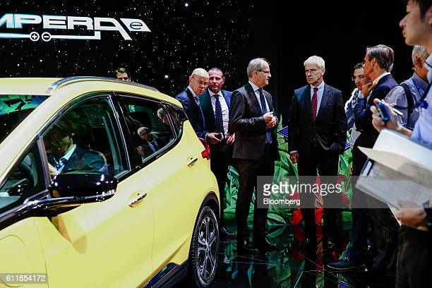 Matthias Mueller, chief executive officer of Volkswagen AG, center right, stands beside a Opel AG Ampera-e electric automobile on the second press...