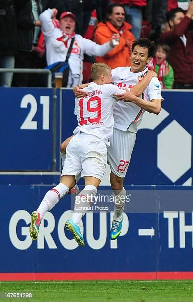 Matthias Ostrzolek and DongWon Ji of Augsburg celebrate a goal during the Bundesliga match between FC Augsburg and VfB Stuttgart at SGL Arena on...