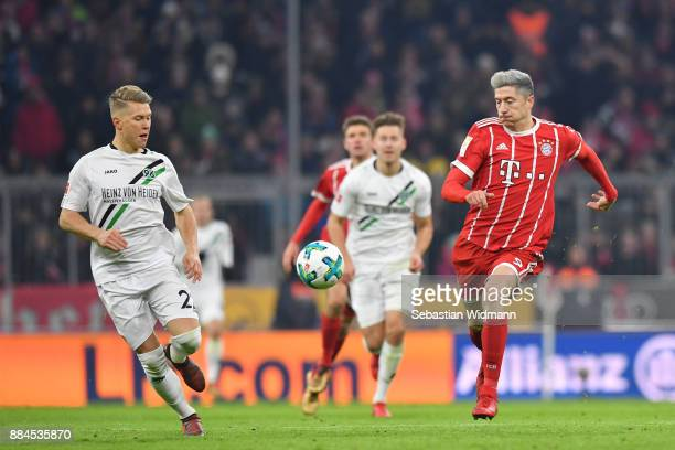 Matthias Ostrzolek of Hannover and Robert Lewandowski of Bayern Muenchen run towards the ball during the Bundesliga match between FC Bayern Muenchen...