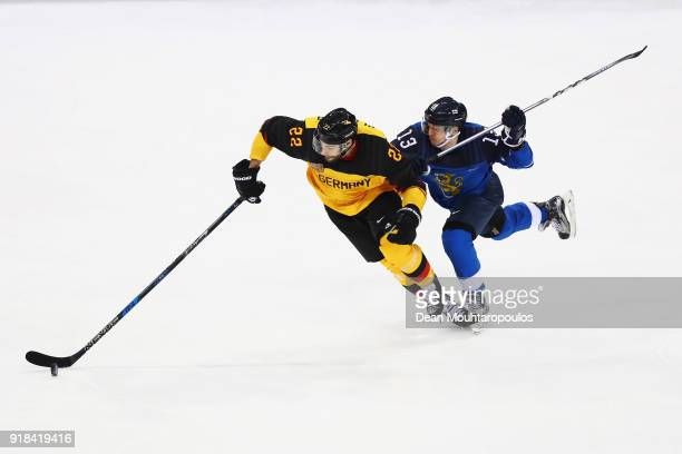 Matthias Plachta of Germany battles for the puck with Julius Junttila of Finland during the Men's Ice Hockey Preliminary Round Group C game on day...