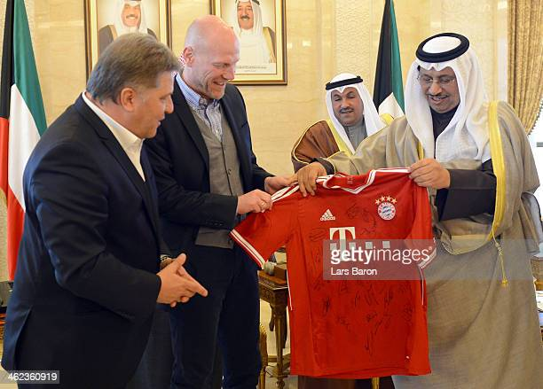 Matthias Sammer, sporting direcotr of Bayern Muenchen, and Markus Hoerwick, director media of Bayern Muenchen, present a jersey to Shaikh Jaber...