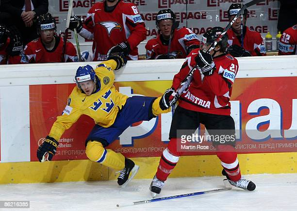 Matthias Trattnig ofAustria tackles Tobias Enstrom of Sweden at the board during the IIHF World Ice Hockey Championship preliminary round, group C...