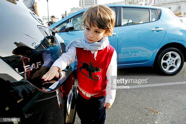 Matthieu Chalouhi looks at his reflection in the back of his father's newlypurchased Nissan Motor Co Leaf electric car in San Francisco California US...