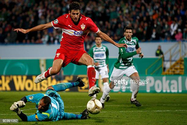 Matthieu Delpierre of Stuttgart jumps over goalkeeper Stephan Loboue of Greuther Fuerth during the DFB Cup match between SpVgg Greuther Fuerth and...