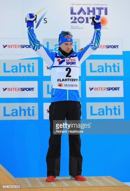 Matti Heikkinen of Finland celebrates winning a Bronze medal in the Men's Cross Country Mass Start during the flower ceromeny during the FIS Nordic...