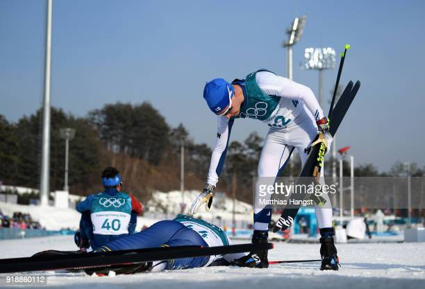 Matti Heikkinen of Finland speaks to Calle Halfvarsson of Sweden as he lies on the ground after finishing the CrossCountry Skiing Men's 15km Free at...