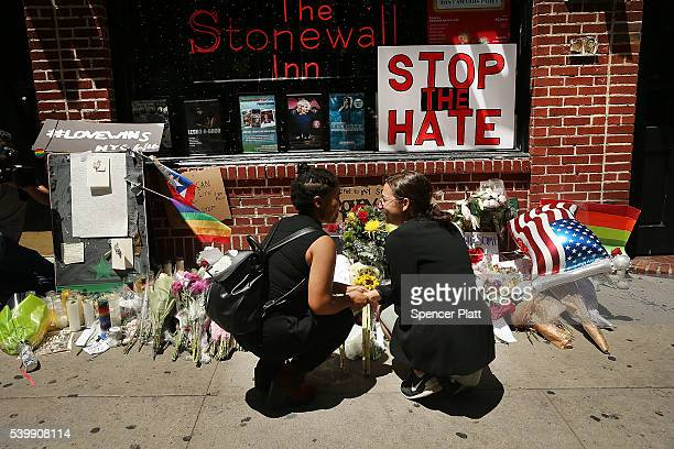 Matti Mejia and Shaina Roberts pause in front of the iconic gay and lesbian bar The Stonewall Inn to lay flowers and grieve for those killed in...