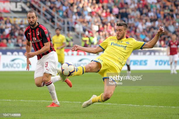 Mattia Bani of AC Chievo Verona competes for the ball with Gonzalo Higuain of AC Milan during the serie A match between AC Milan and Chievo Verona at...