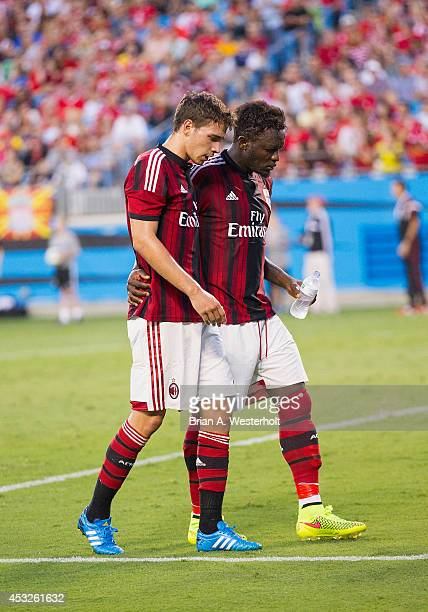 Mattia De Sciglio of AC Milan is helped off the field by teammate Sulley Muntari after being injured in a collision with goalkeeper Gabriel during...