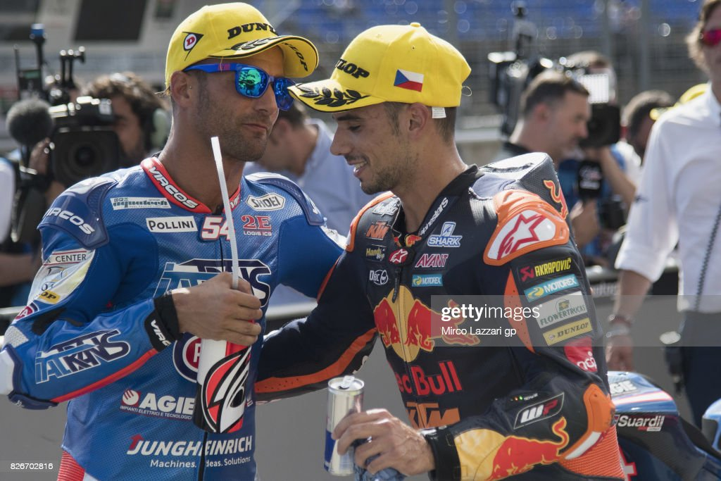 Mattia Pasini of Italy and Italtrans Racing Team celebrates with Brad Binder of South Africa and Red Bull KTM Ajo (R) at the end of the qualifying practice during the MotoGp of Czech Republic - Qualifying at Brno Circuit on August 5, 2017 in Brno, Czech Republic.