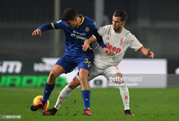 Mattia Pessina of Hellas Verona competes for the ball with Mirelam Pjanic of Juventus during the Serie A match between Hellas Verona and Juventus at...