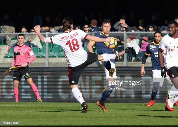 Mattia Vallotti of Hellas Verona competes wuth Riccardo Montolivo of AC Milan during the Serie A match between Hellas Verona FC and AC Milan at...