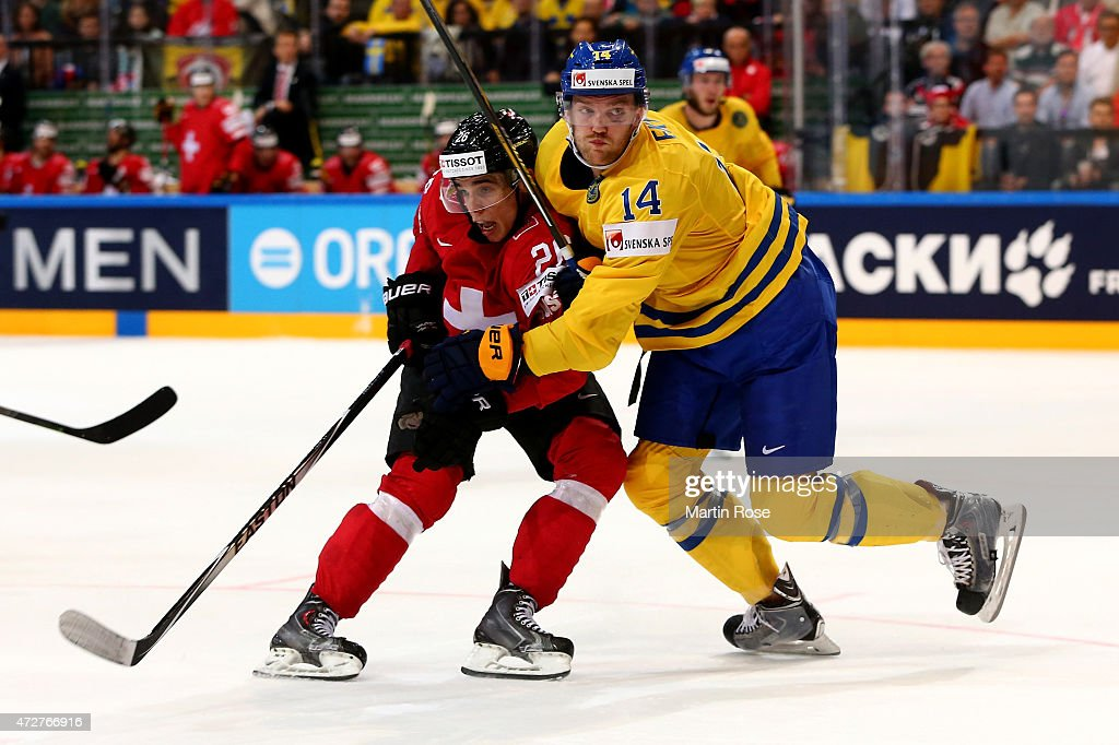 Mattias Ekholm (R) of Sweden and Reto Suri (L) of Switzerland battle for the puck during the IIHF World Championship group A match between Austria and Switzerland at o2 Arena on May 9, 2015 in Prague, Czech Republic.