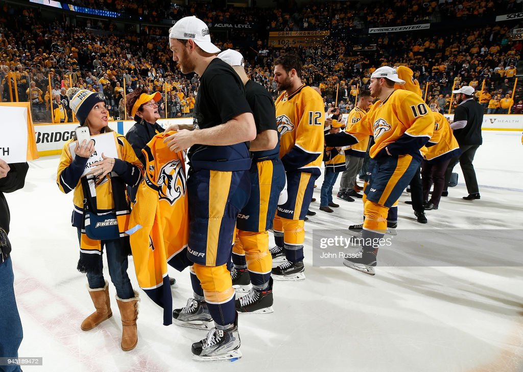 Mattias Ekholm #14 of the Nashville Predators gives his jersey to a fan after a 4-2 win against the Columbus Blue Jackets during an NHL game at Bridgestone Arena on April 7, 2018 in Nashville, Tennessee.