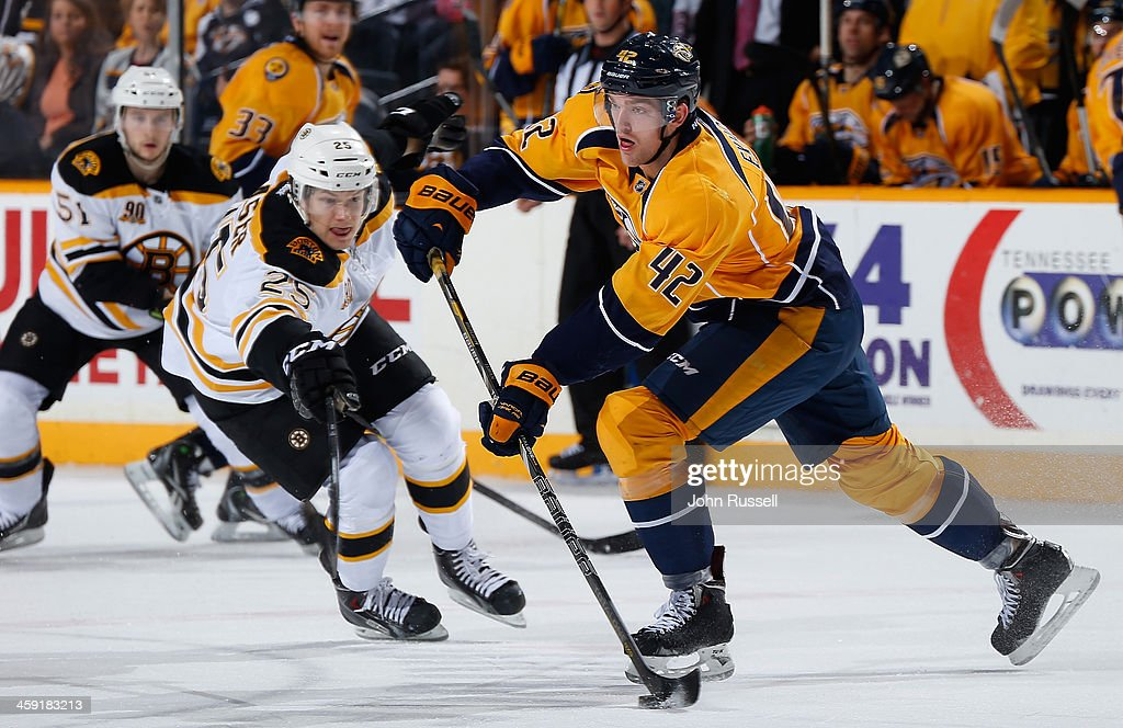 Mattias Ekholm #42 of the Nashville Predators passes the puck against Matt Fraser #25 of the Boston Bruins at Bridgestone Arena on December 23, 2013 in Nashville, Tennessee.
