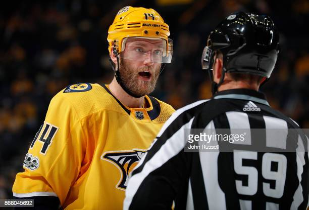 Mattias Ekholm of the Nashville Predators talks with linesman Steve Barton during a break in play against the Calgary Flames during an NHL game at...