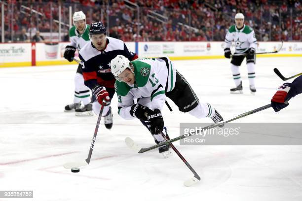 Mattias Janmark of the Dallas Stars and Dmitry Orlov of the Washington Capitals go after the puck in the first period at Capital One Arena on March...