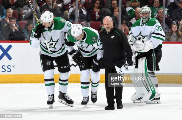 Mattias Janmark of the Dallas Stars is assisted off the ice by teammate Roope Hintz and head athletic trainer Dave Zeis after an injury during the...