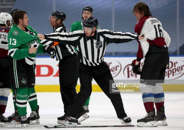 Mattias Janmark of the Dallas Stars is kept away from Nikita Zadorov of the Colorado Avalanche by linesman Pierre Racicot during the third period of...