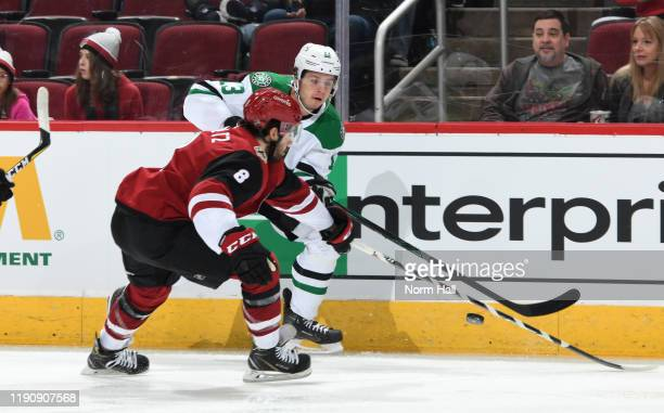 Mattias Janmark of the Dallas Stars plays the puck past the defense of Nick Schmaltz of the Arizona Coyotes during the first period of the NHL hockey...