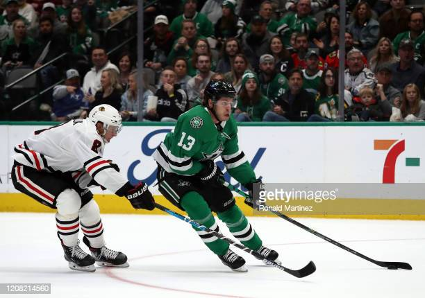 Mattias Janmark of the Dallas Stars skates the puck against Dominik Kubalik of the Chicago Blackhawks in the first period at American Airlines Center...