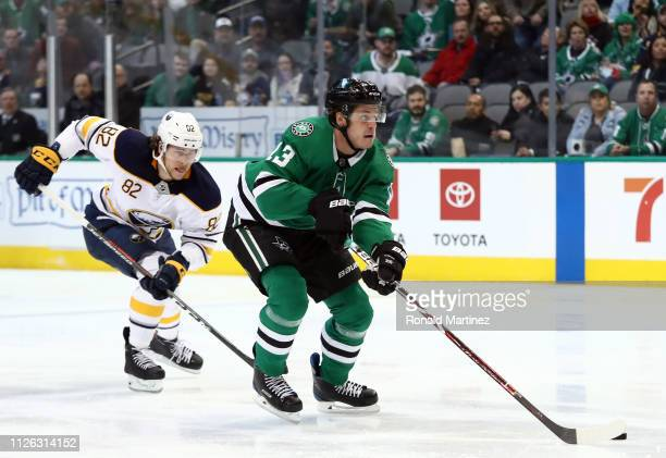 Mattias Janmark of the Dallas Stars skates the puck against Nathan Beaulieu of the Buffalo Sabres in the first period at American Airlines Center on...